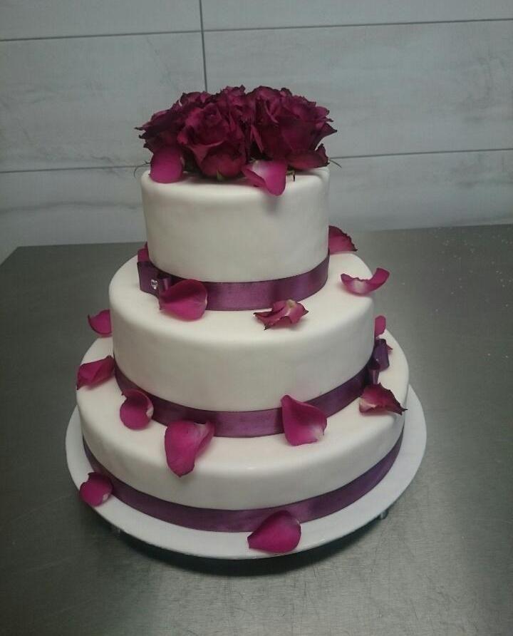Tort weselny pokryty masą cukrową strojony żywymi płatkami róż w kolorze głębokiego fioletu.