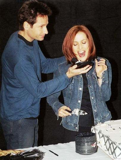 Because it's Friday, and because it's in between both of their birthdays, and also because of these nicely coordinated black t-shirt andjean jacket, matching blue long-sleeved t and pants ensembles, here is a photograph of David and Gillian and some cake.
