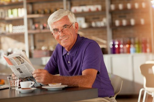 Man reading newspaper in cafe