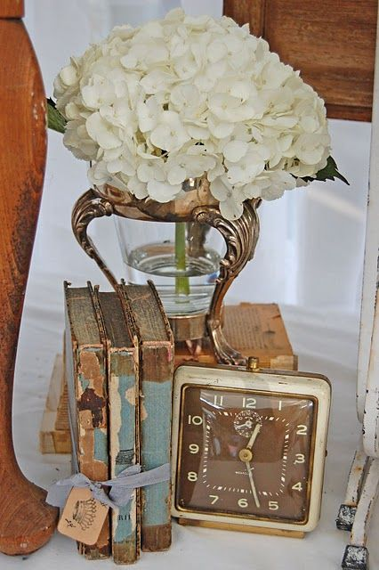 Tarnished silver looks amazing for vintage wedding reception centerpieces, especially love it with hydrangeas, see our rental silver, vases, clocks, and books like seen in this picture for rent at southernvintagegeorgia.com