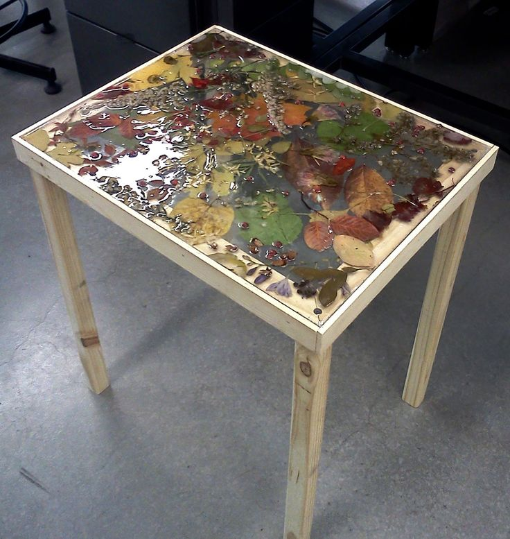resin ideas | Pressed leaves and plants in resin on handcrafted table.