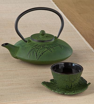 Bamboo Grove Cast Iron Teapot and Cup and Saucer—heavy, durable, beautiful! Next to water, tea is the most popular beverage in the world. And it was discovered by accident! According to Chinese folklore, Emperor Shen Nung believed that water should be boiled before drinking. On a summer voyage in 2737 BCE, his servants boiled water to drink, and leaves from a camellia bush blew into the water. The Emperor loved the aroma, tasted the water, and found it delicious. And that's how tea was born!