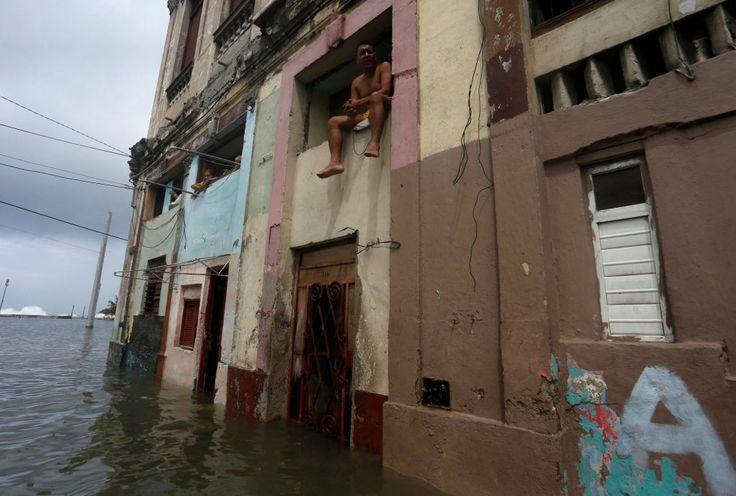 Un cubano sentado sobre el alféizar de una ventana de su casa, afectada por las inundaciones provocadas por el Irma.