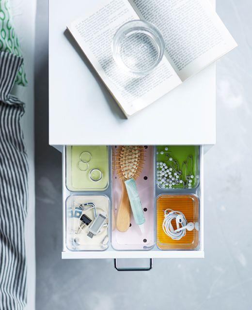 Eine geöffnete Schublade, in der transparente GODMORGON Fächer mit verschiedenen Gegenständen darin zu sehen sind