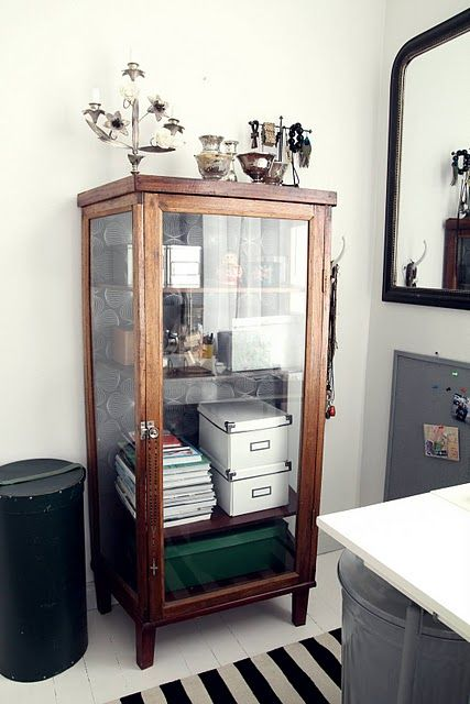 """Idea for updating curio cabinet """"A wallpaper-backed glass-fronted cabinet is full, but still manages to look interesting and stylish."""" Like the boxes inside also ❥"""