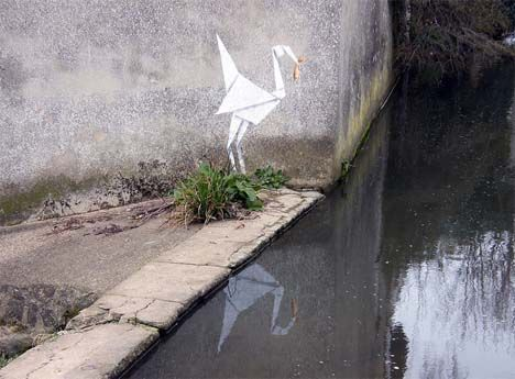 "Banksy's latest piece, features a stenciled ""Origami Stork"" holding a goldfish located on a wall beside a river."