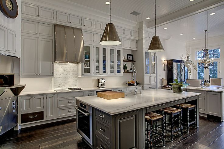 Stunning kitchen design in white and silver, with a pizza oven, butcher block, pot filling faucet and other pro quality accessories.  From a 4-story Craftsman style home construction by Lavallee Construction, discovered on Porch.com