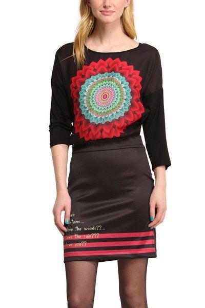 Desigual-jurk model Cenit. Een zwarte jurk met lange mouwen, een korte strakke rok en een lichtere bovenkant. De jurk heeft een grote, typische Desigual-versiering in het midden en hele coole teksten op de rok.