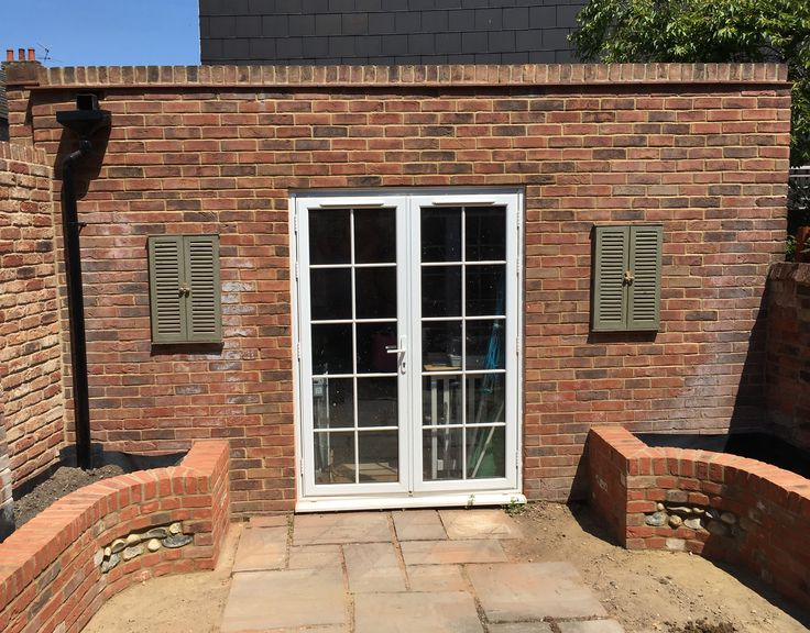Mirrored brick retaining walls with flint panels