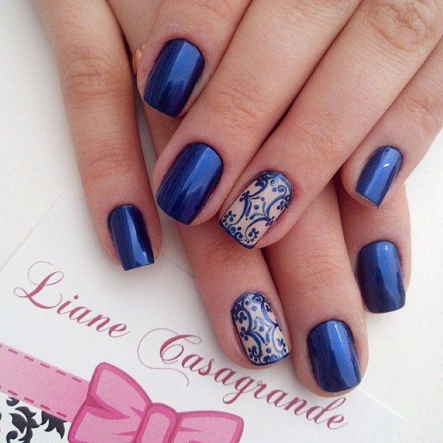 Unhas azul metálico e bege com decoração abstrata.