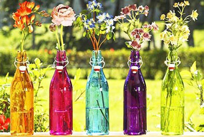Garrafas coloridas com arranjos de flores para enfeitar a casa