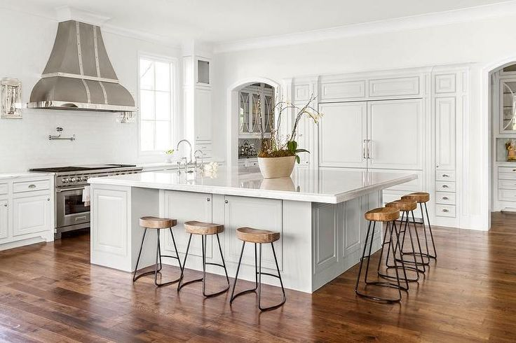 Beautiful kitchen features an oversized island topped with white marble fitted with a farm sink, facing the cooktop, lined with Wisteria Smart & Sleek Stools.