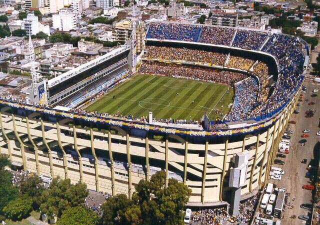 "Estadio Bombonera. Three sides of the Bombonera are made up of traditional stands. However, the fourth side had to be built vertically, with several seating areas stacked one on top of the other, to stay within the stadium's property.The unusual shape of the stadium has led to it having excellent acoustics and the Boca support being nicknamed ""La Doce"" (The 12th man) La Bombonera is renowned for vibrating when fans start to jump in rhythm."