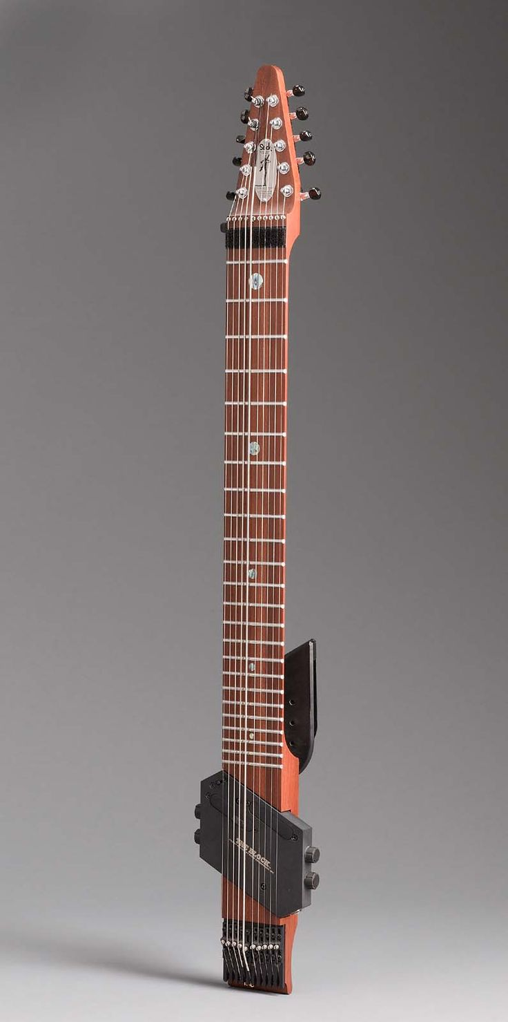 Chapman Stick, a.k.a., The Stick : : originally devised by Emmett Chapman in the early 1970s, it is played by tapping or fretting the strings [rather than plucking them] with both hands simultaneously. Sticks are designed in 8, 10 or 12 string models by Stick Enterprises.