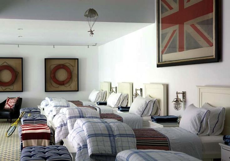 nehomemag.com  Robert Dean - boys' bedroom. Framed Union Jack, red lifesavers framed in black shadow boxes, ivory twin beds, marine sconces, red & blue striped bedding, blue tufted ottomans and yellow & gray rug.