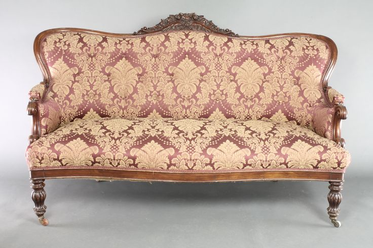 """Lot 862, An early Victorian carved mahogany show frame sofa, the carved cresting rail decorated flower heads and upholstered in red and floral patterned material, the seat of serpentine outline, raised on turned and reeded supports 40 1/2""""h x 63""""w x 34""""d, est  £400 - 600"""