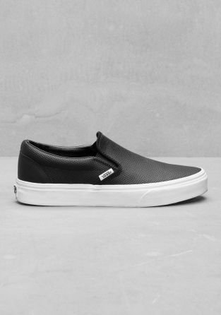 VANS Classic slip-ons featuring a perforated leather upper, fine stitching, and the Vans logo sewn to the outer edge.
