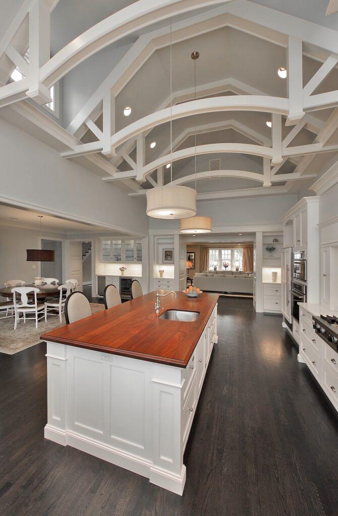 С видом из противоположного конца кухни, мы лучше посмотрим на встроенное освещение и мансардных окон в потолочном пространстве.  В столовой можно увидеть слева, с темным деревянным столом и белые стулья сосредоточенных над цветочной коврика.