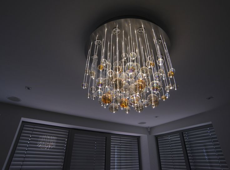 Modern chandelier made of hand blown glass hanging on sparkling fiber optics. Night mode.