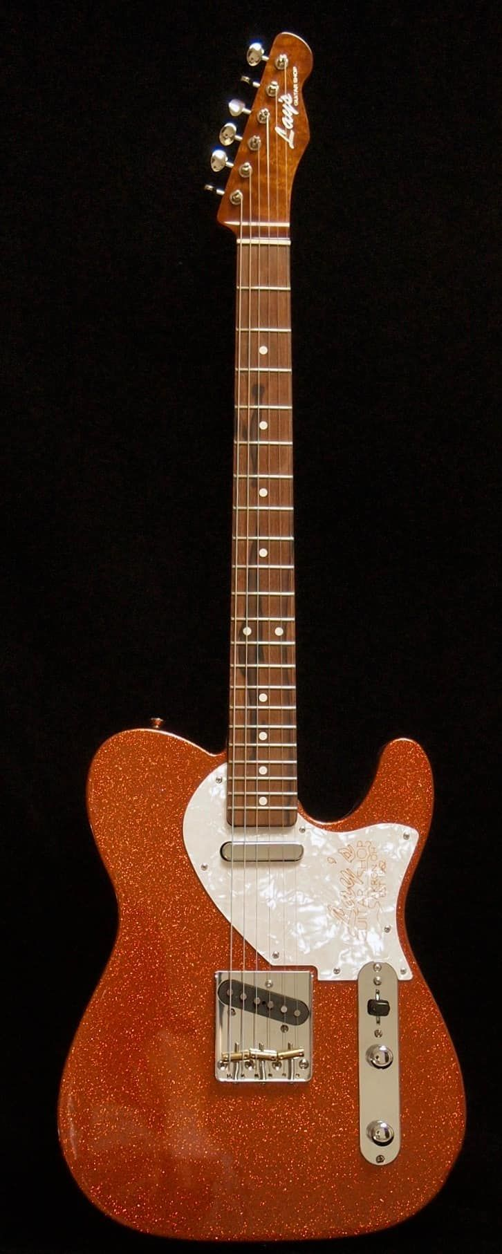 """Here is a totally custom-made, one-of-a-kind Lay's Guitar Shop Burnt Orange Sparklecaster. It has some really great features including the following:Alder BodyFlamed Sapele NeckBrazilian Rosewood Fret Board12"""" RadiusBone 1 11/16"""" NutVintage Neck Construction (single action truss rod)6105 Fret..."""