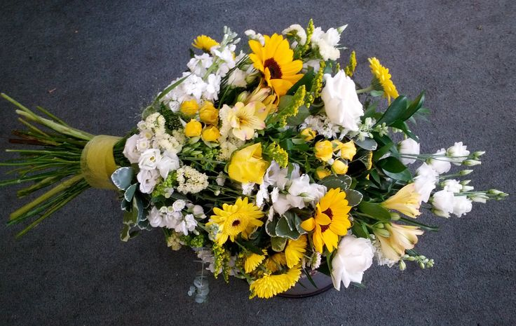 Tied sheaf in yellow and white with sunflowers, gerberas, lisianthus, roses.