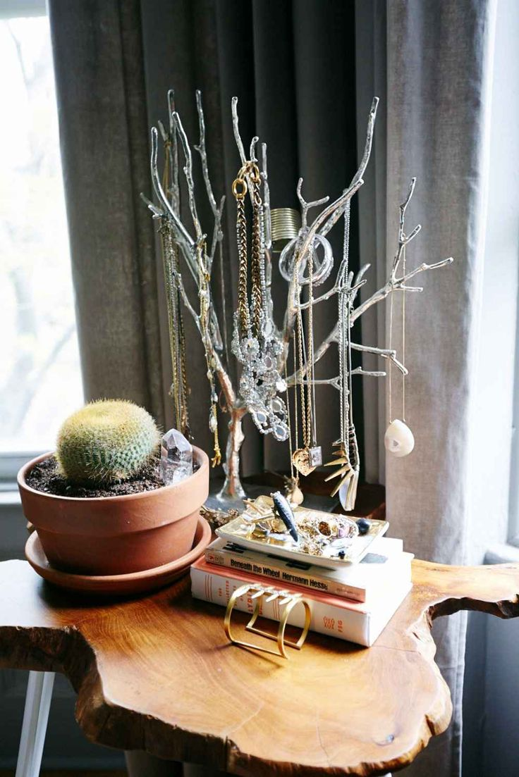 Try small pieces with big impact.  The rough-hewn wood-slab side table and sliver jewelry tree keep Abby's things organized, yet playful looking. Each one's got an earthy vibe and together, with the potted cactus and crystal, the display is almost boutique-like.