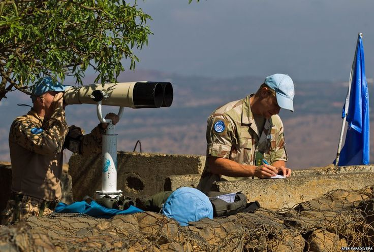 UN peacekeepers through strong binoculars watch fighting near the Syrian town of Quneitra and the Quneitra crossing on the Golan Heights, 29 August 2014, the day after 43 Fijian peacekeepers were kidnapped.