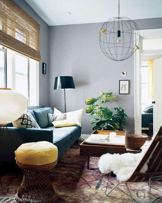Sala pequena com sofá verde, luminária pendente  redonda de arame, manta sobre a cadeira, banqueta de vime, mesa de centro aberta.