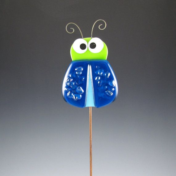 The Crazy Bug Plant Stake is made from fused glass. I used a strong epoxy to attach it to a 12 metal rod. The paint accents are permanently fired onto the glass. He also has some cute curly antenna and some clear iridescent chips of glass for the texture on his wings.    Glass Size - 3 wide x 4.25 high including antenna  (7.6cm x 10.8cm)    ***If you are purchasing several plant sticks please contact me with your zip code. You may be able to save on shipping!***    All of the pieces are…