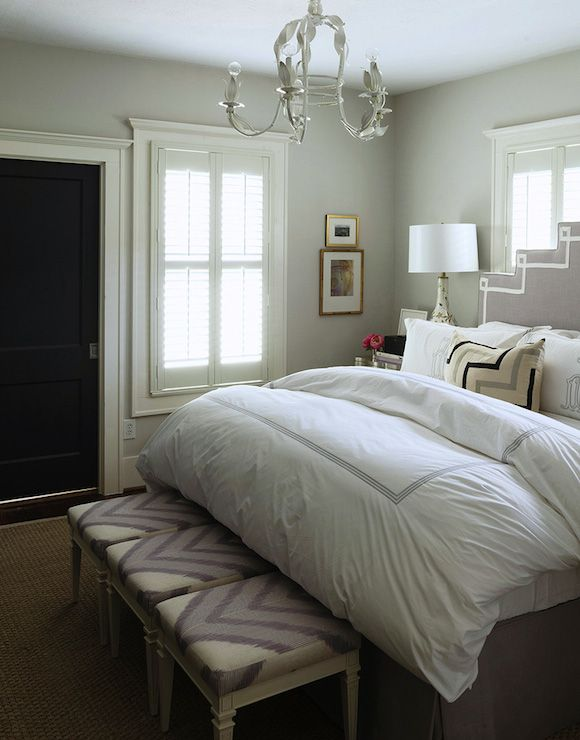 Stunning bedroom features white tole chandelier over gray, art deco headboard accented with white ribbon trim on queen bed placed in front of window dressed in hotel bedding and monogrammed shams alongside three chevron stools at foot of the bed.