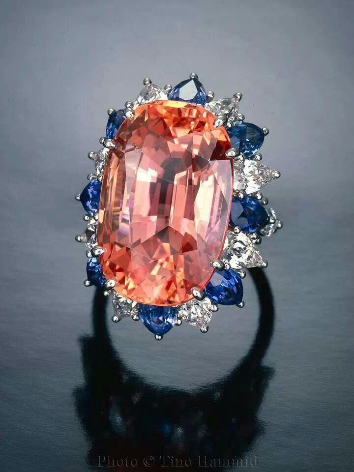 30-karat Padparadscha sapphire  surrounded by blue sapphires and diamonds. Gorgeous color combo~