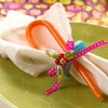 Wrapped in Color  Present basic white cloth napkins with a punch of Christmas color. These holly bead napkin rings take just a few crafting supplies and are finished with a sweet candy cane as a favor for guests.