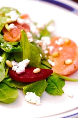 Spinach and beet salad with goat cheese, pine nuts, grapefruit, and homemade dressing made with grapefruit juice, agave nectar, vinegar and olive oil
