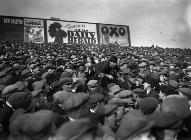 1st March 1930: A good tempered football crowd at West Ham, London pass a young boy over their heads to the front so that he can see the game better. (Photo by S. R. Gaiger/Topical Press Agency/Getty Images)