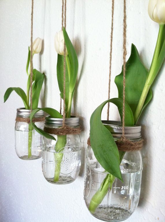 Super cool and super simple mason jar wall vases, hung with twine in a row with green leaves against a white wall. Filled with a single white tulip each - it's crisp and clean with no caffeine.