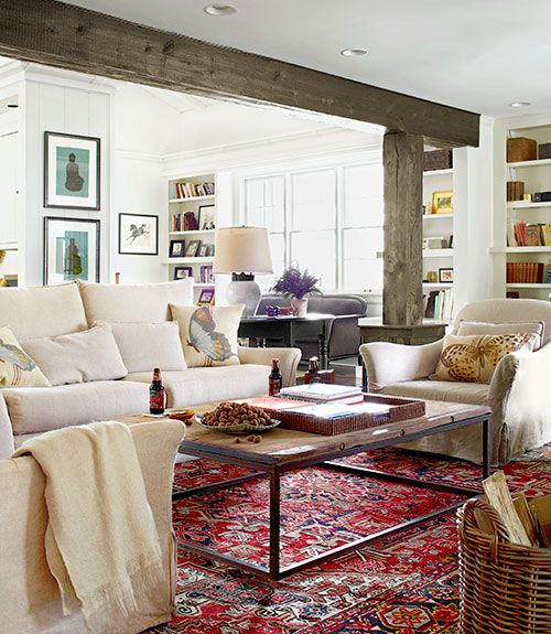 exposed beams + white palette + built-in shelving + rug + wood coffee table