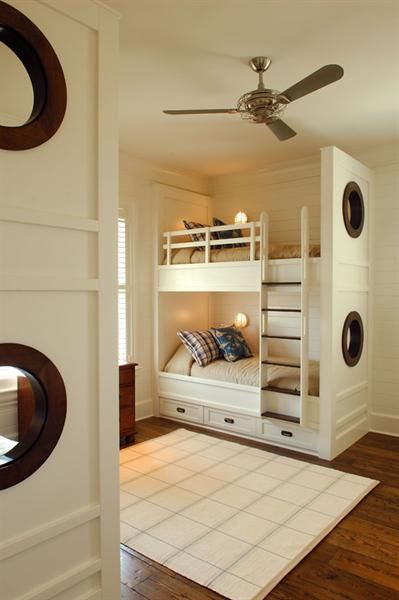 Bunk Room with nautical themed portholes, under bed storage and individual bed windows | Phillip W Smith portfolio