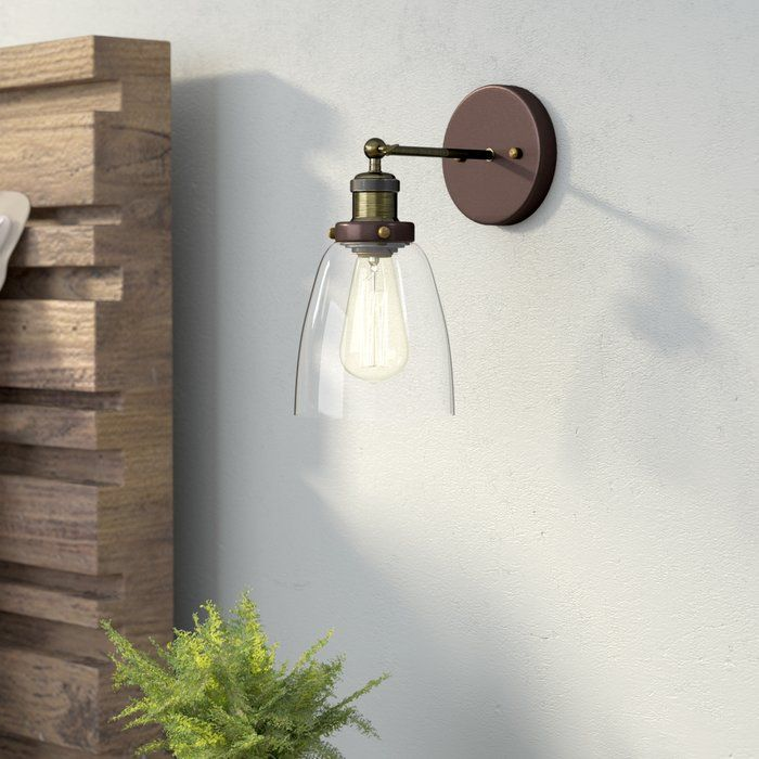 Masterfully mixing clean-lined design with rustic details, this charming one-light wall sconce is the perfect piece to illuminate your space in understated style. Featuring steel construction in a timeless oil-rubbed bronze finish, this charismatic design includes a circular backplate, an angular arm, and a gently curved seeded glass shade around a fashionable Edison bulb. For an upscale, tailored look in your master bedroom, install this light over a reclaimed wood nightstand on each side…