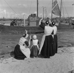 Urk, vrouwen en kind in klederdracht zwaaien vissersboot uit Collectie Stadsarchief Amsterdam #Urk
