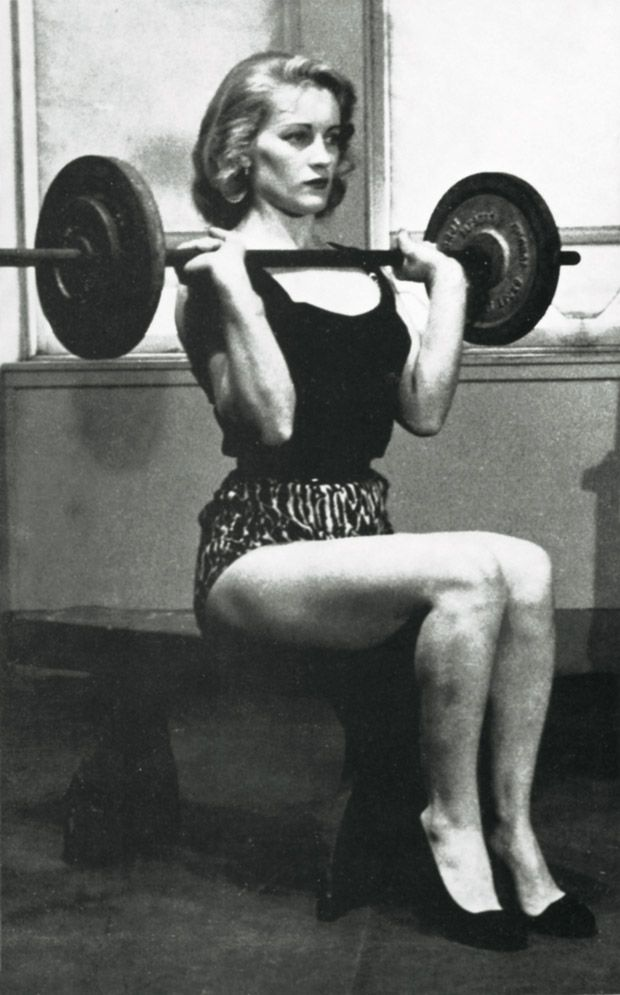 """We should bring this back!   """"From the mid-1950s to the early 1970s, women had to appear as ladylike as possible, even when doing something as traditionally masculine as working out with weights. This girl is doing a seated press with respectably heavy weight, but her high heels and helmet0like hairdo are like fig leaves preserving her femininity."""""""