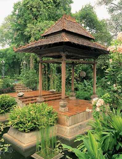 "The joglo, or gazebo, has carving typical of Java's Kudus region. Brotodiwirjo, who landscaped the gardens, describes it as a spot for enjoying tea amid ""water lilies of many pastel shades."" He notes, ""The area is then filled with rattan sofas and chairs with soft cushions."""