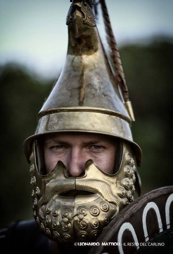 Reenactor wearing a bronze Phrygian helmet. The skull of the helmet was usually raised from a single sheet of bronze, though the forward-pointing apex was sometimes made separately and riveted to the skull. The skull was often drawn out into a peak at the front, this shaded the wearer's eyes and offered protection to the upper part of the face from downward blows. The face was further protected by large cheekpieces, made separately from the skullpiece.