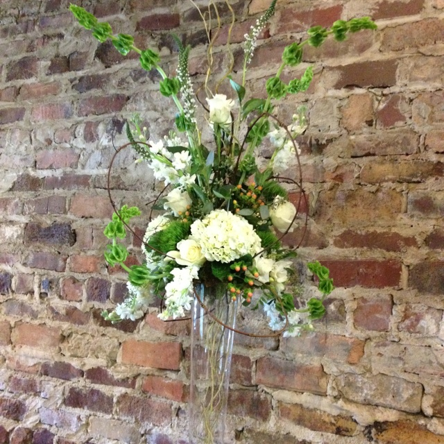 Tall arrangement with white and green flowers and twisted grape vine