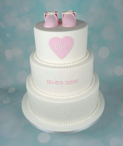 White tiered baptism cake with pink shoes and heart detail
