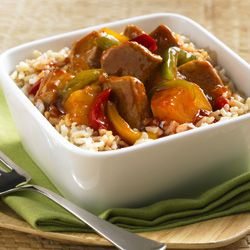 Pork tenderloin with bell peppers and pineapple in sweet and sour sauce over rice