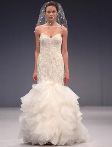 Anne Barge Angélique is a strapless lace mermaid gown with three dimensional petal embroidery and organza skirt. This gown came from a designer bridal boutique and is in excellent condition. Anne Barge Angélique is Pearl and a size 8.