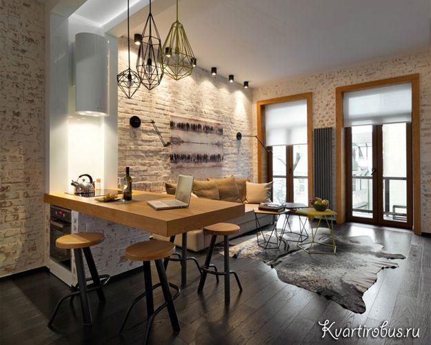 Бежевая гостиная в стиле лофт на фото объединена с кухней. Отсутствие…
