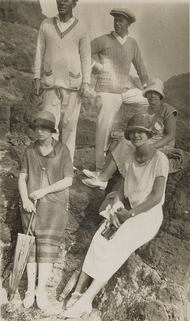 Group at the seaside by State Library of Victoria Collections, via Flickr. Women wearing three-quarter length shift dresses with cloche hats, men in light coloured slacks and peaked caps. The women are seated or leaning back against foreshore rocks while the men are standing on rocks behind them. Melbourne Victoria Australia