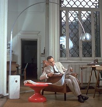 """Achille Castiglioni in his studio, under an """"Arco"""" lamp (1962), sitting on """"Sanluca"""" chair, next to a """"Rochcetto"""" table."""