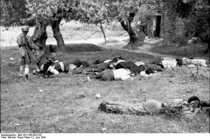 German Nazi paratrooper fires his pistol into Cretan villagers massacred by the Germans at Kondomari, Crete, Greece, June 1941.